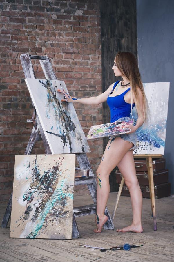 Jonge vrouwelijke kunstenaar die abstract beeld in studio schilderen, mooi sexy vrouwenportret royalty-vrije stock afbeeldingen