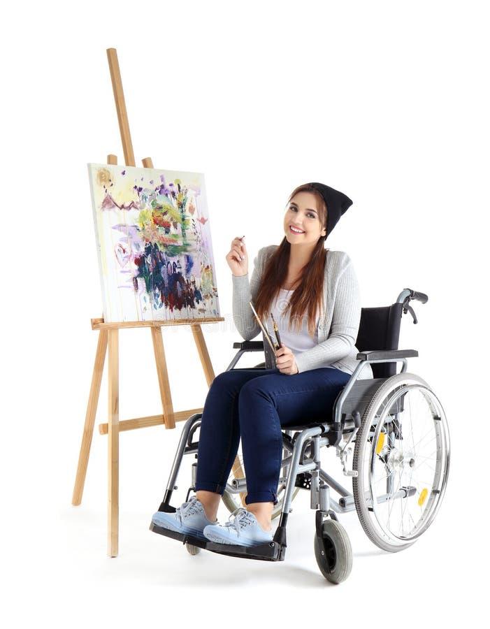 Jonge vrouwelijke kunstenaar in rolstoel het schilderen beeld op witte achtergrond stock foto's