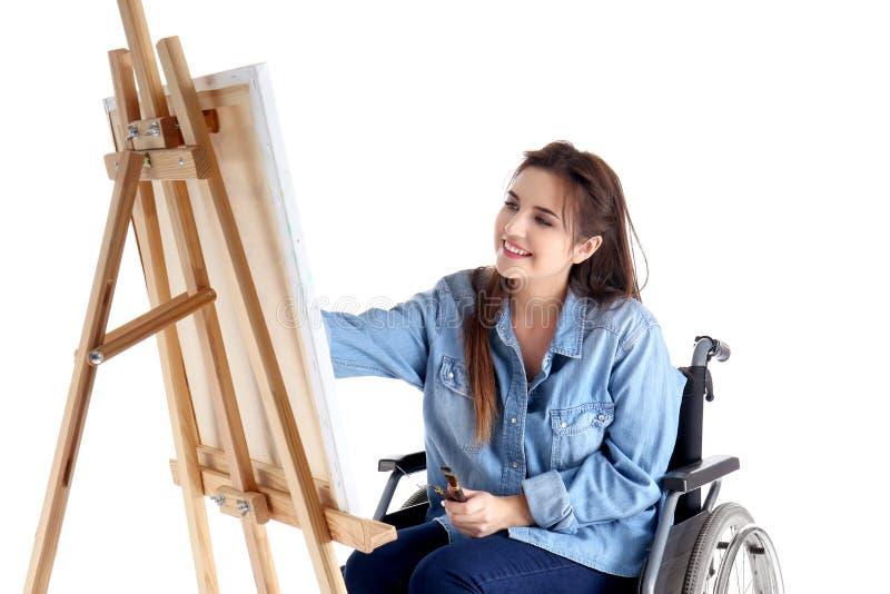 Jonge vrouwelijke kunstenaar in rolstoel het schilderen beeld op witte achtergrond royalty-vrije stock afbeelding