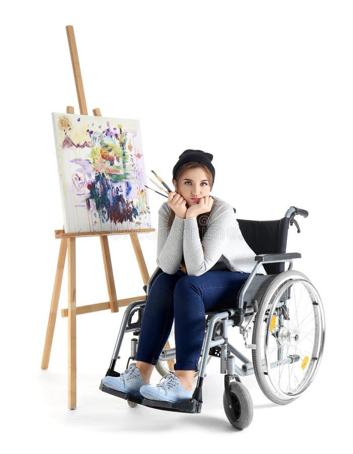 Jonge vrouwelijke kunstenaar in rolstoel het schilderen beeld op witte achtergrond royalty-vrije stock fotografie