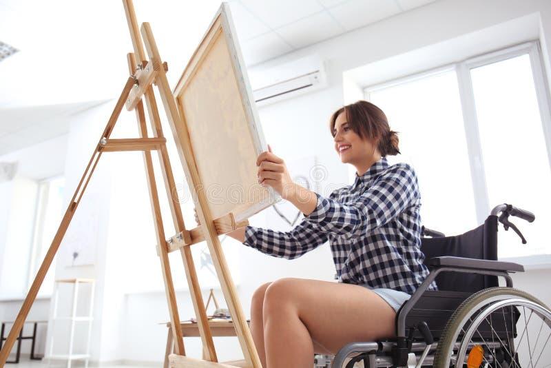 Jonge vrouwelijke kunstenaar in rolstoel het schilderen beeld thuis royalty-vrije stock foto