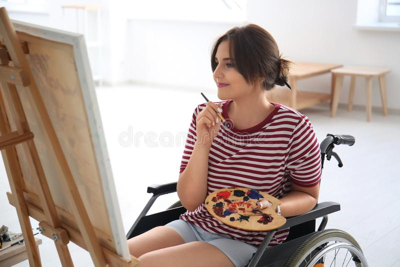 Jonge vrouwelijke kunstenaar in rolstoel het schilderen beeld thuis royalty-vrije stock afbeeldingen