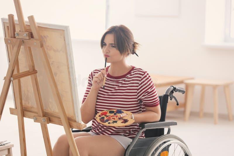 Jonge vrouwelijke kunstenaar in rolstoel het schilderen beeld thuis stock foto's