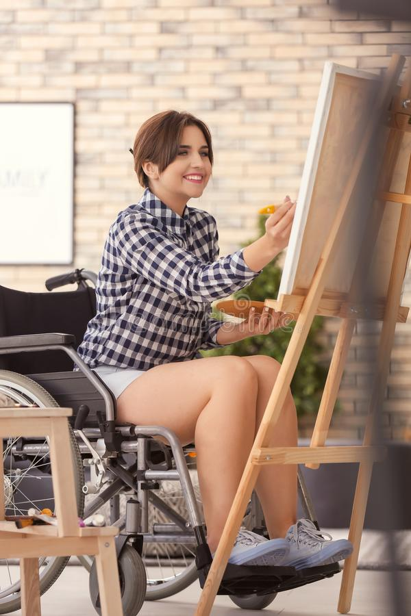 Jonge vrouwelijke kunstenaar in rolstoel het schilderen beeld thuis royalty-vrije stock foto's