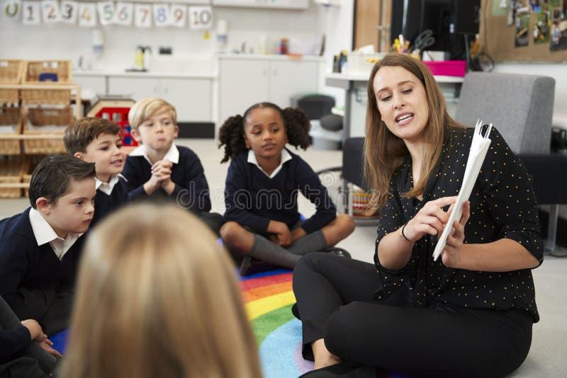 Jonge vrouwelijke lage schoolleraar die een boek lezen aan kinderen die op de vloer in een klaslokaal, selectieve nadruk zitten stock foto