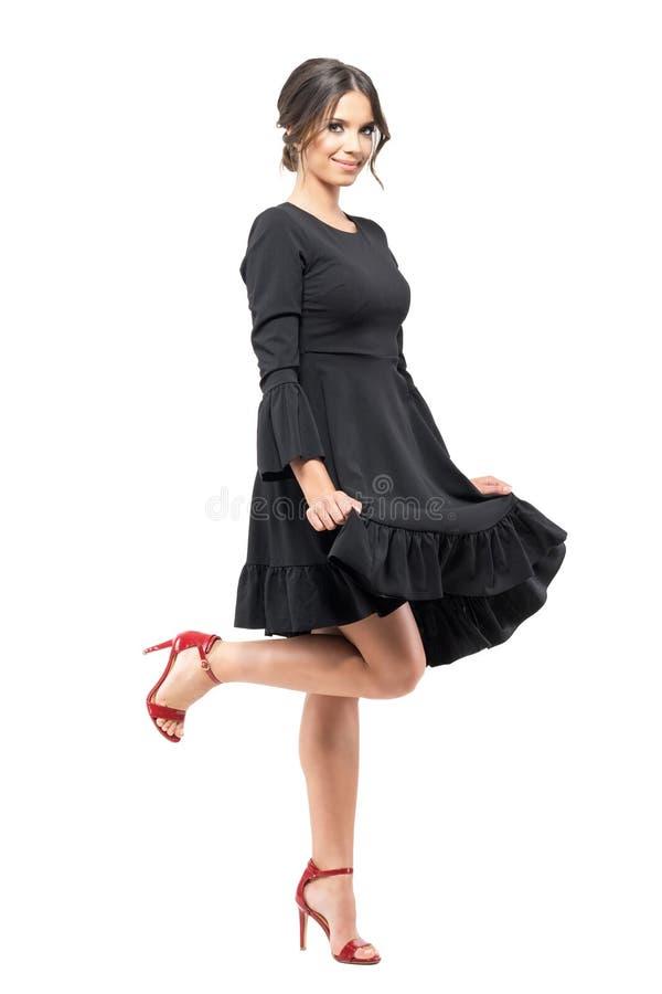 Jonge vrouwelijke Latijnse danser in zwarte stromende flounce kleding die en bij camera dansen glimlachen royalty-vrije stock afbeeldingen
