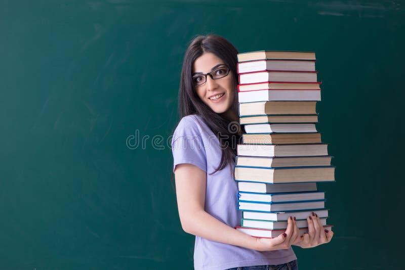 Jonge vrouwelijke leraarsstudent voor groene raad royalty-vrije stock foto