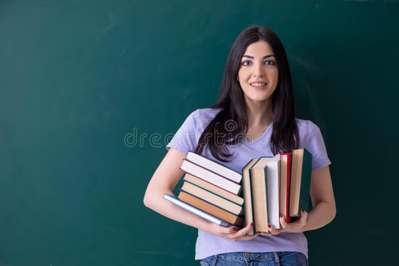 Jonge vrouwelijke leraarsstudent voor groene raad stock afbeeldingen