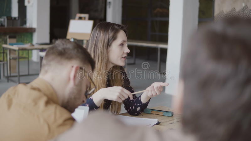 Jonge vrouwelijke manager die richting geven aan haar team Multi-etnische groep mensen bij ochtend planning in zolderbureau stock foto's
