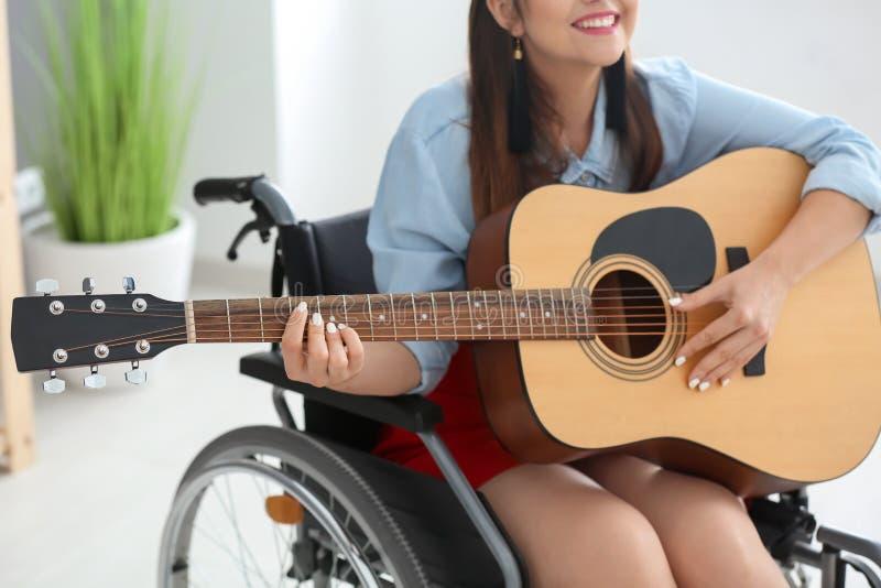 Jonge vrouwelijke musicus in rolstoel het spelen gitaar thuis stock foto's