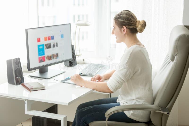 Jonge vrouwelijke ontwerper die thuis bureau werken bij computer royalty-vrije stock afbeeldingen