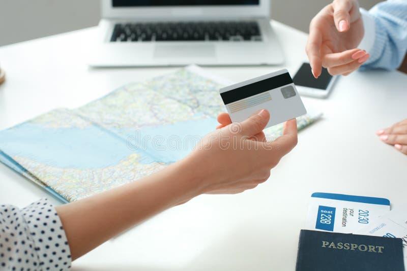 Jonge vrouwelijke reisbureauadviseur in reisagentschap met een betaling van de klantencreditcard royalty-vrije stock foto's