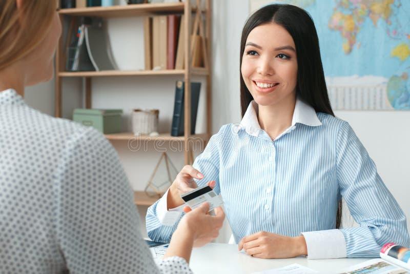Jonge vrouwelijke reisbureauadviseur in reisagentschap met een klantenbetaling royalty-vrije stock afbeelding