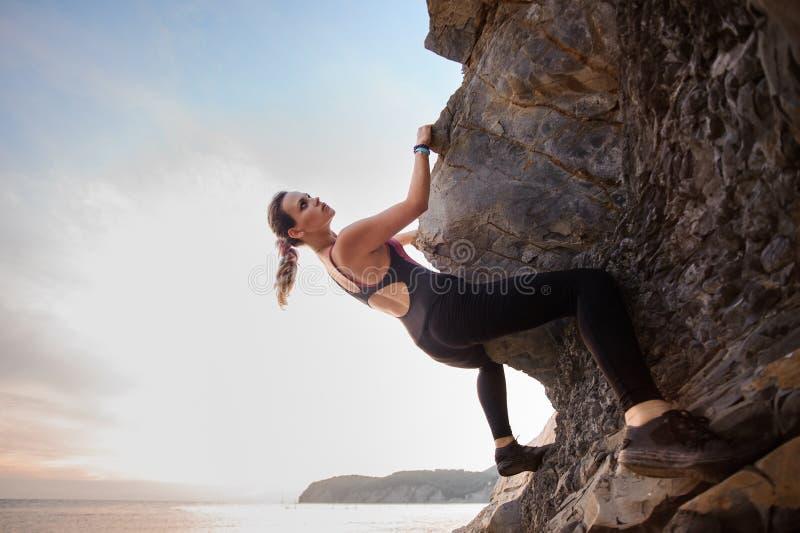 Jonge vrouwelijke rotsklimmer die uitdagingsroute op overhangende klip beklimmen stock fotografie