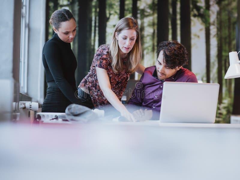 Jonge vrouwelijke stafmedewerker die haar ideeën voorstellen aan collega's stock foto's