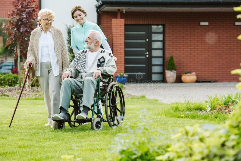 Jonge vrouwelijke stagiair met ouder paar in de tuin royalty-vrije stock afbeelding