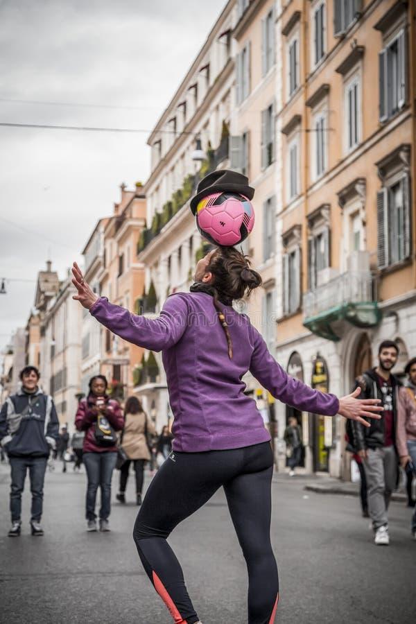 Jonge vrouwelijke straatentertainer die met haar voetbal in de straten van Rome presteren stock afbeeldingen
