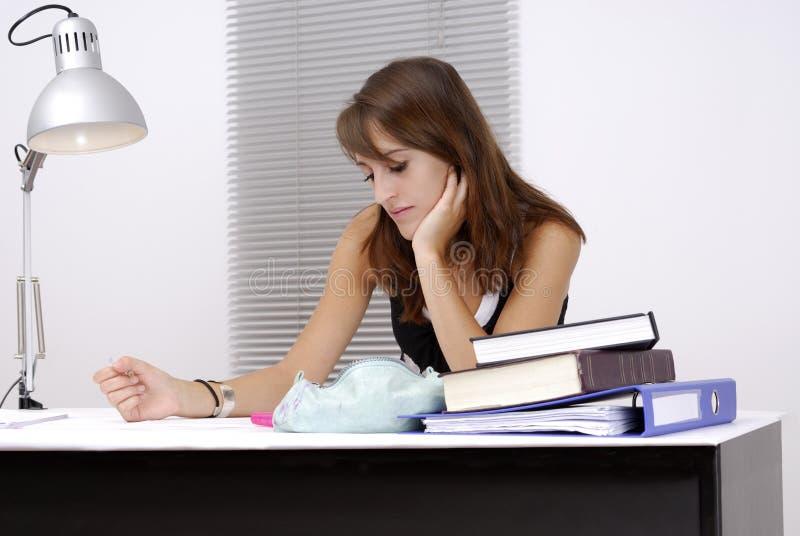 Jonge vrouwelijke student bij haar bureau royalty-vrije stock afbeeldingen