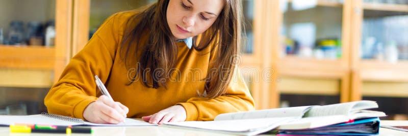 Jonge vrouwelijke student in chemieklasse, het schrijven nota's Geconcentreerde student in klaslokaal stock fotografie