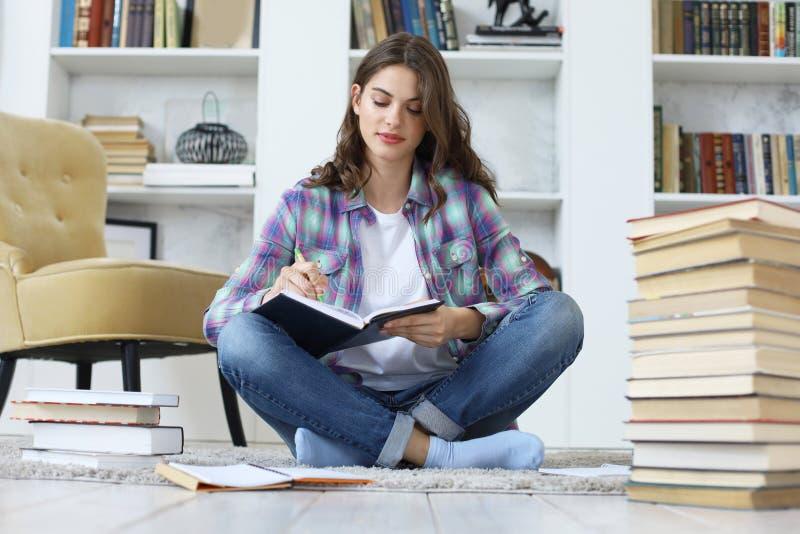 Jonge vrouwelijke student die, op vloer tegen comfortabel binnenlands binnenland zitten thuis bestuderen die, die met stapel van  royalty-vrije stock foto's