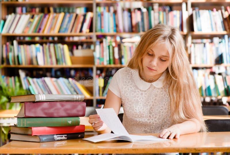 Jonge vrouwelijke student die taken in bibliotheek doen stock fotografie