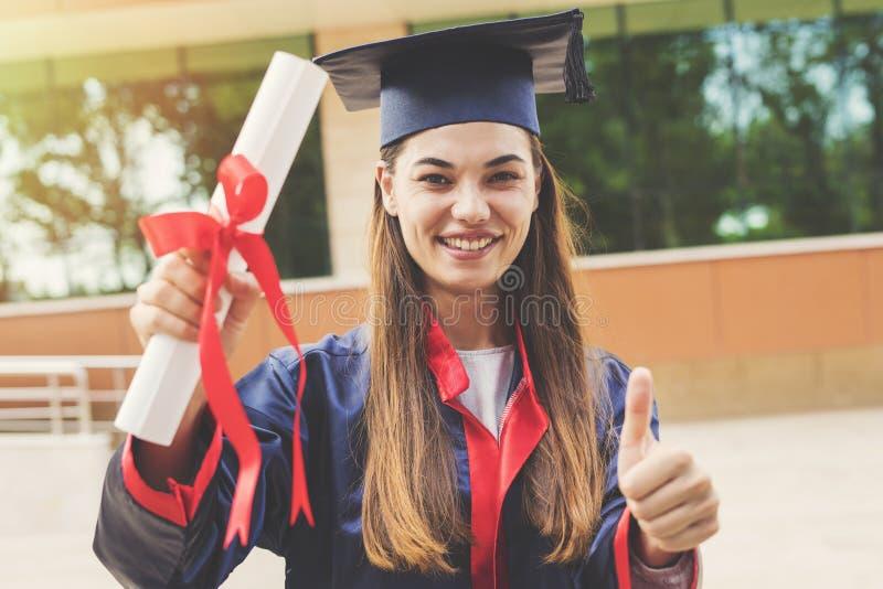 Jonge vrouwelijke student die van universiteit een diploma behalen stock foto's