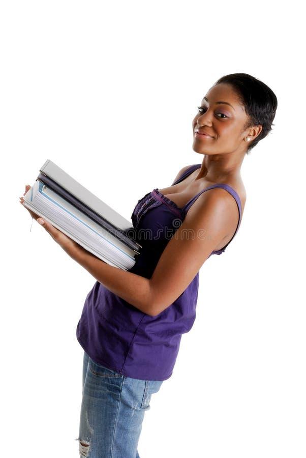 Jonge vrouwelijke studenten dragende boeken stock fotografie