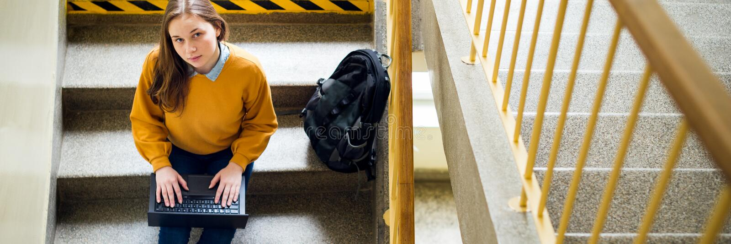 Jonge vrouwelijke studentzitting op treden op school, het schrijven poging op haar laptop en het bekijken omhoog de camera Onderw stock foto