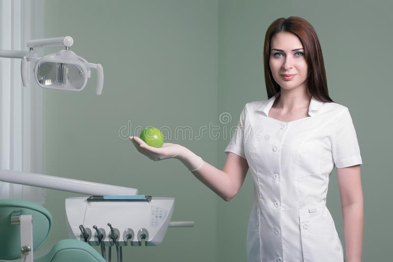 jonge vrouwelijke tandarts met groene appel in hand op achtergrond van medisch bureau royalty-vrije stock foto's