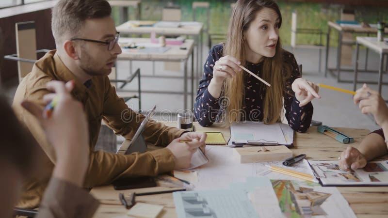 Jonge vrouwelijke teamleider die met kleine multiraciale groep mensen spreken Commerciële vergadering van startbedrijf in bureau stock afbeelding
