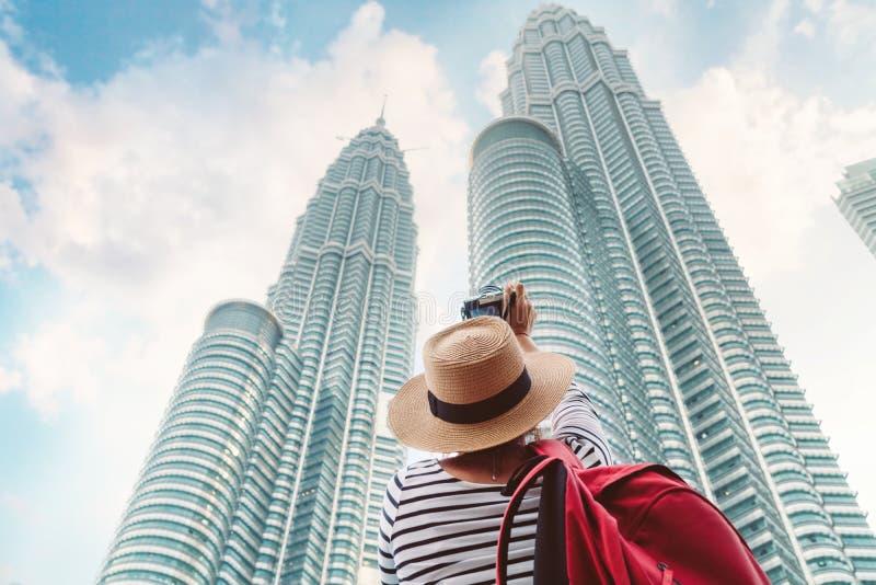 Jonge vrouwelijke toerist die beeld maken dat van twee wolkenkrabberstorens wordt geschoten in grote Aziatische stad royalty-vrije stock foto's