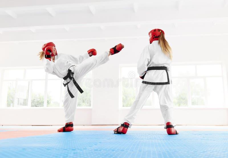 Jonge vrouwelijke vechter die gebruikend de schop en de stempel van de karatetechniek in dozen doen stock afbeelding