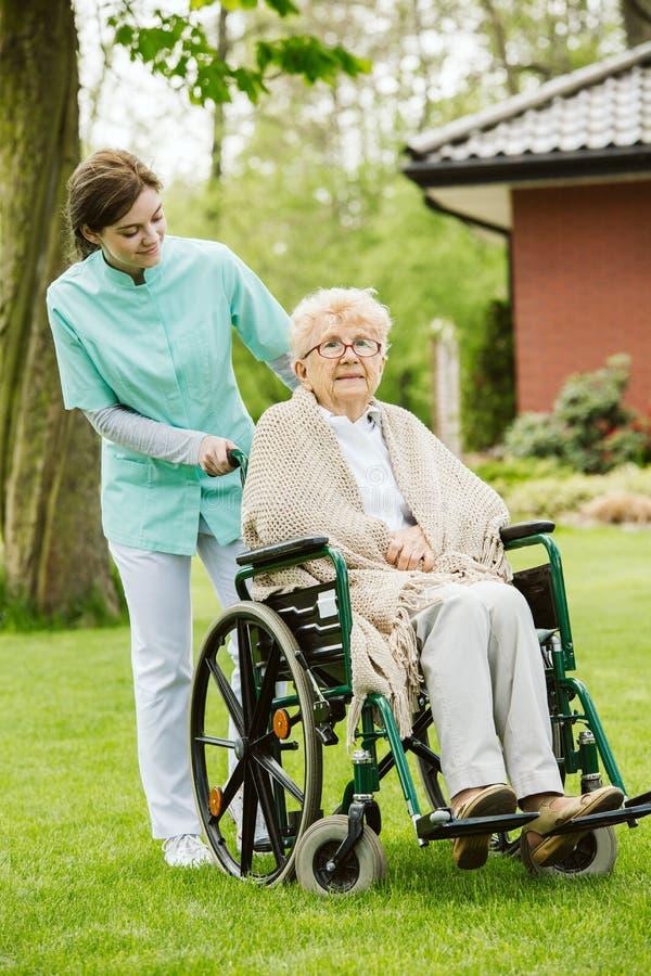 Jonge vrouwelijke verpleegster met gehandicapten in de tuin stock foto's