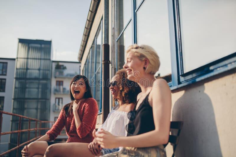 Jonge vrouwelijke vrienden die in terras genieten van stock foto's