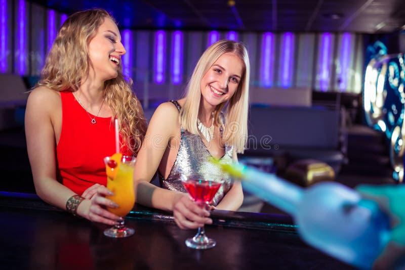 Jonge vrouwelijke vrienden die van dranken in nachtclub genieten royalty-vrije stock afbeelding