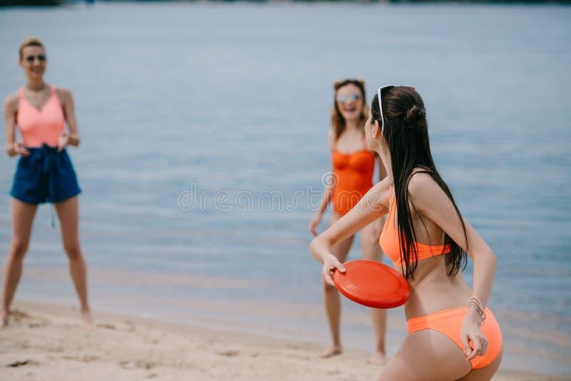 jonge vrouwelijke vrienden in het swimwear spelen met vliegende schijf stock fotografie