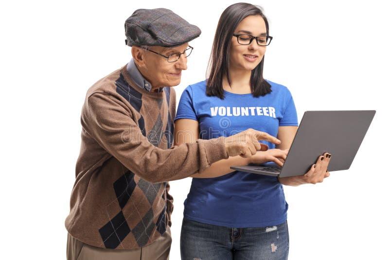 Jonge vrouwelijke vrijwilliger die een bejaarde met een laptop computer helpen stock foto