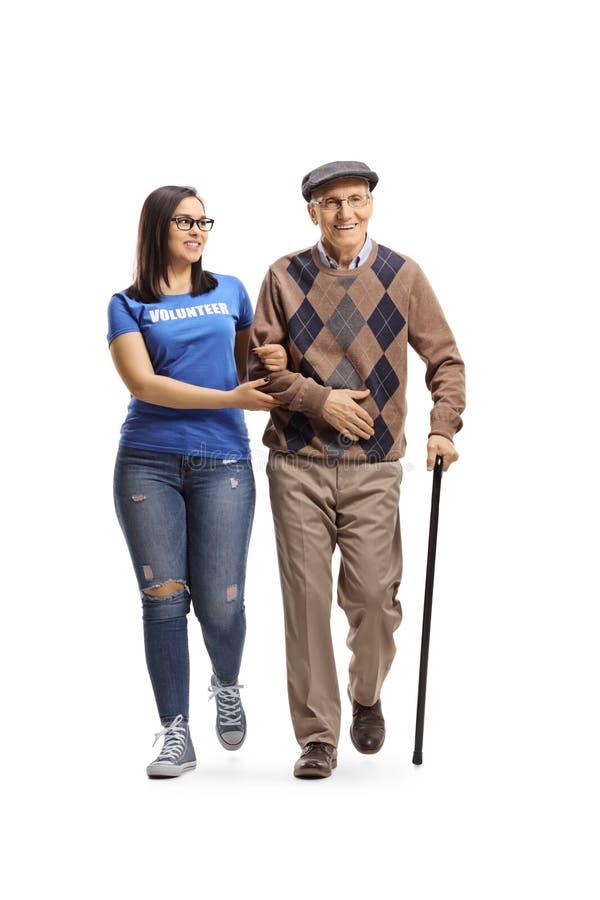 Jonge vrouwelijke vrijwilliger die een bejaarde met een riet helpen royalty-vrije stock foto