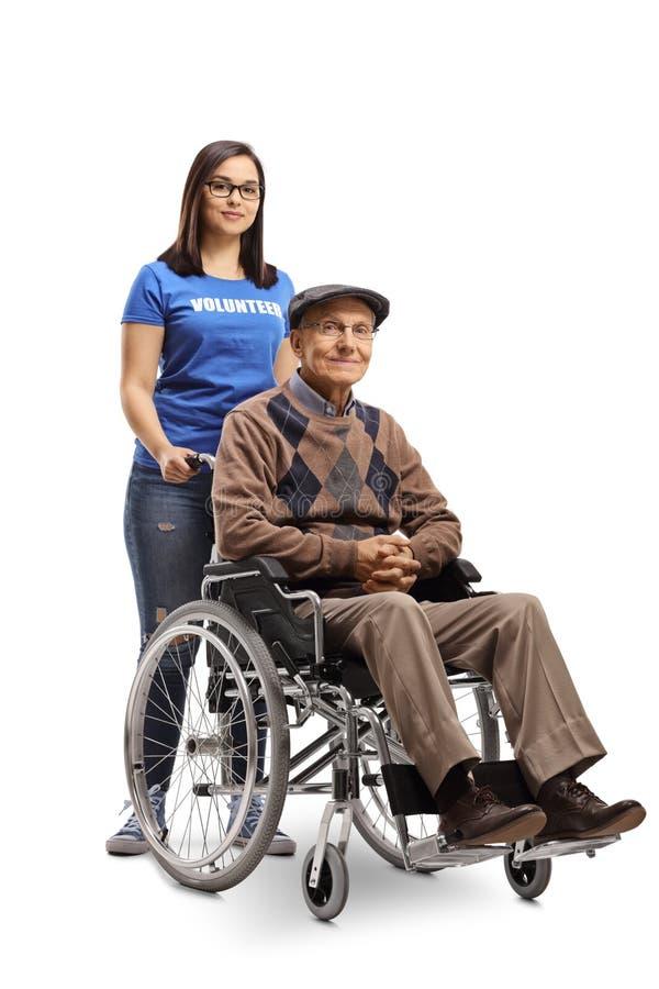 Jonge vrouwelijke vrijwilliger die een bejaarde in een rolstoel helpen stock foto