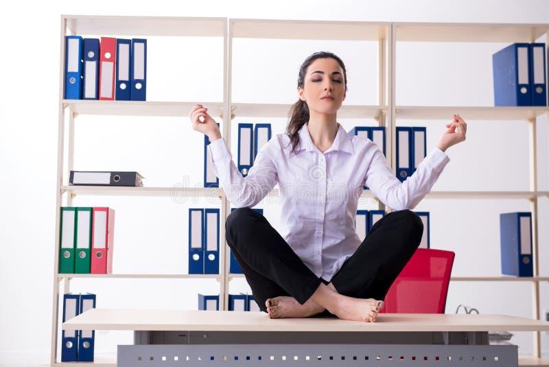 Jonge vrouwelijke werknemer die oefeningen in het bureau doen stock fotografie