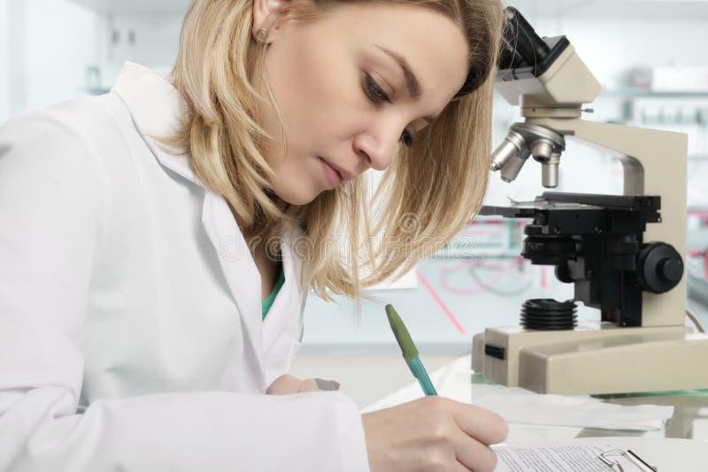 Jonge vrouwelijke wetenschapper die in modern laboratorium schrijven stock afbeelding