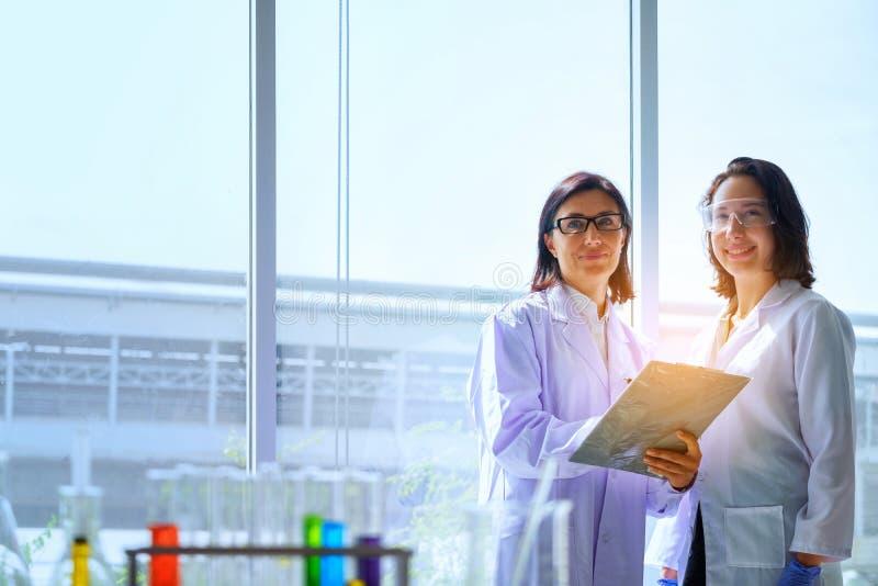 Jonge vrouwelijke wetenschapper die zich met techer in laboratoriumarbeider het maken bevinden stock fotografie