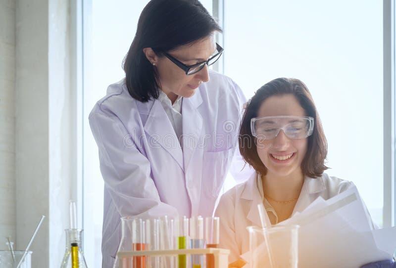 Jonge vrouwelijke wetenschapper die zich met techer in laboratoriumarbeider het maken bevinden stock afbeeldingen