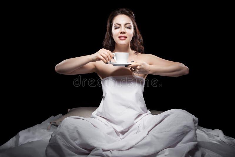 Jonge vrouwelijke zitting in bed en het drinken koffie; royalty-vrije stock fotografie
