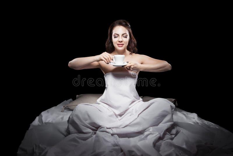 Jonge vrouwelijke zitting in bed en het drinken koffie; stock afbeeldingen