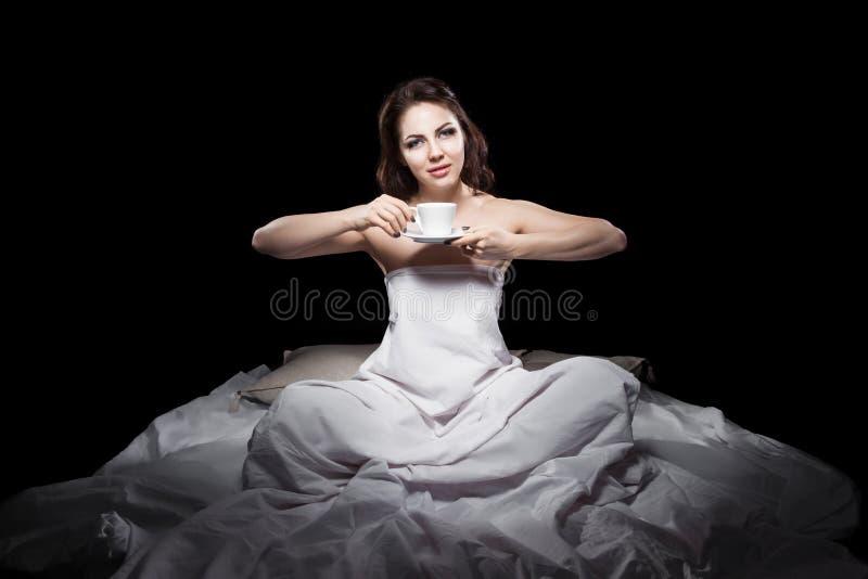 Jonge vrouwelijke zitting in bed en het drinken koffie; royalty-vrije stock foto's