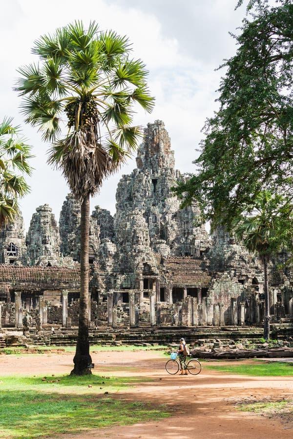 Jonge vrouwen berijdende fiets naast Bayon-tempel in Angkor complexe Wat, Kambodja stock afbeelding