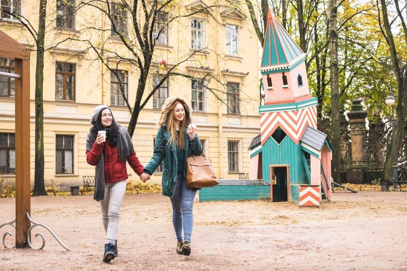 Jonge vrouwen beste vrienden die de winter van tijd genieten samen openlucht stock foto