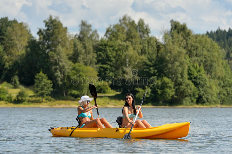 Gelukkige meisjes die op zonnige dag kayaking stock foto's