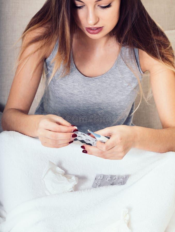 Jonge vrouwen blazende neus in bed ziek met temperatuur stock afbeeldingen